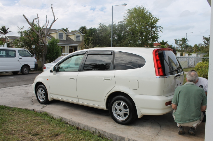 On Wednesday, we went to the place of the man selling us this 2001 Honda Stream.  Nice car, isn't it?   This car is a gift from God that is for sure.  We got it for a far better price than we expected to pay, and it was a far better car than we had anticipated getting.  The story behind this car is fascinating, and if you would like to hear the story, let me know.  I will send you the email of the story I sent to those on our email list. God truly blessed.  Tim and the seller were putting the license plates on the car in this photo.