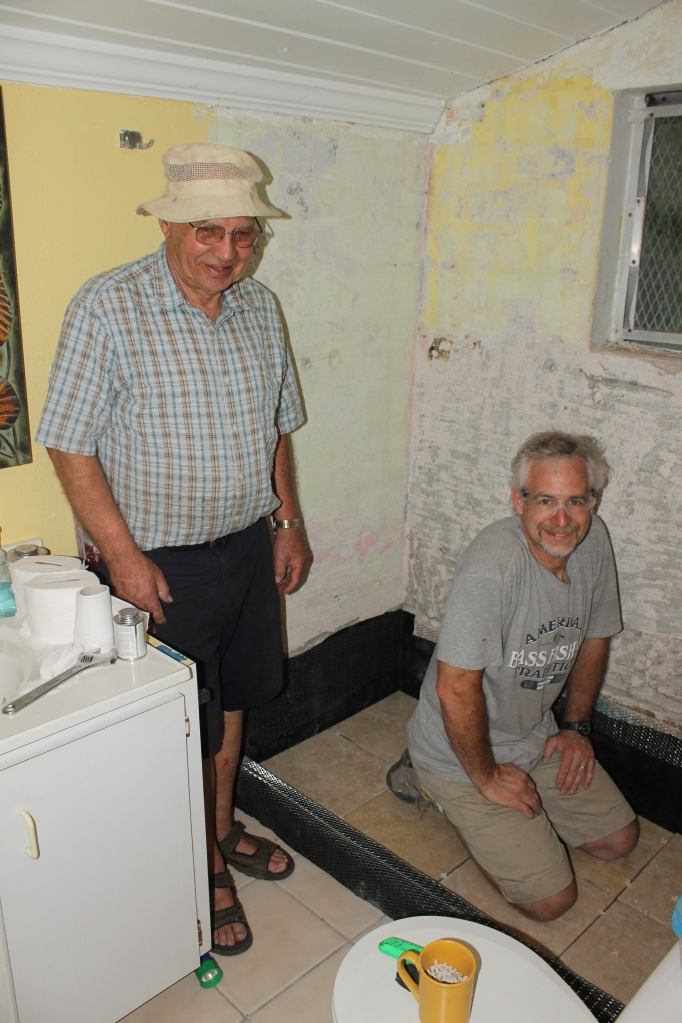 Tim and Bob finishing up the floor tiles in the shower and the plumbing in the shower wall.