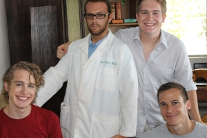 "Michael was ""dressing-up"" to play a part for his role in working with Immersion Camp which took place July 14-20. Notice the name on this lab coat. The name is none other than our dear Ted Habel, MD! In this picture with Logan and Garrett are Michael Chatigny and Nicola (a young man from Switzerland who is here for the summer)."