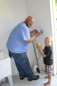 Zeke with his assistant Micah, mapping and labeling wiring in the bath house laundry room and finishing electric fixtures in the bath house so we can get our certificate of occupancy.