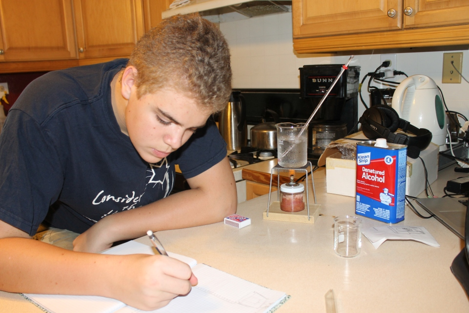 Zachary working on a Chemistry Lab assignment.  It took forever to find that denatured alcohol on this island.