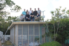 The work crew posing on the roof of the porch.